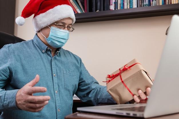 Älterer mann in weihnachtsmannhut und gesichtsmaske gibt ein geschenk und spricht unter verwendung eines laptops für videoanruffreunde und -kinder. weihnachten während des coronavirus. Premium Fotos