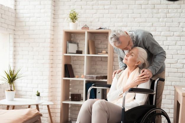 Älterer mann küsst in der reifen frau der stirn im rollstuhl. Premium Fotos