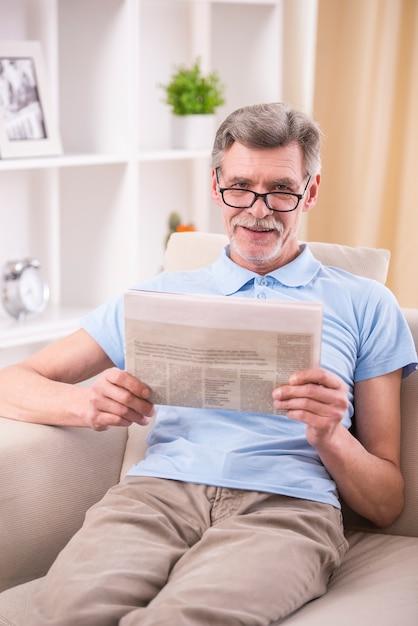 Älterer mann liest zeitung zu hause. Premium Fotos