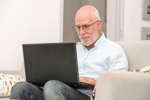 Älterer mann mit dem laptop, der im sofa sitzt Premium Fotos