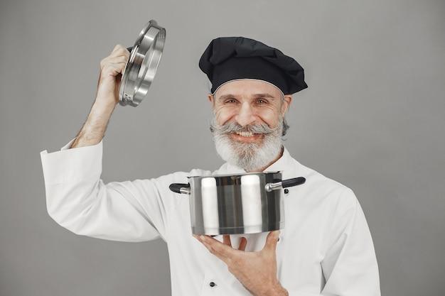 Älterer mann mit metallpfanne. koch in einem schwarzen hut. professionelle herangehensweise an das geschäft. Kostenlose Fotos