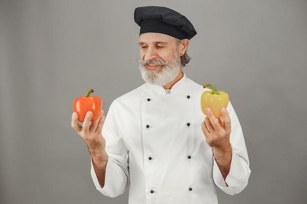 Älterer mann mit rotem und gelbem peper. professionelle herangehensweise an das geschäft. Kostenlose Fotos