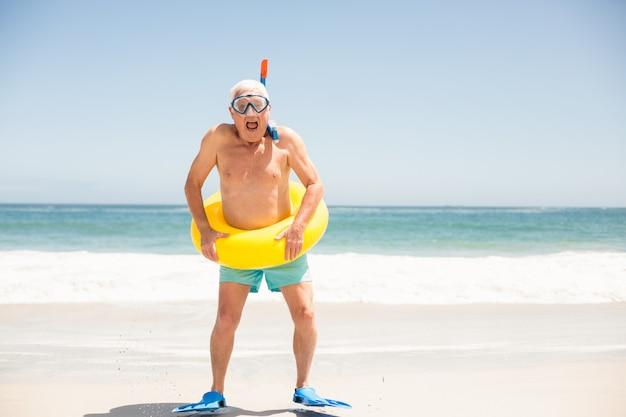 Älterer mann mit schwimmring und flossen am strand Premium Fotos