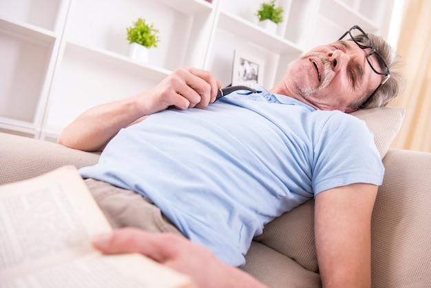 Älterer mann schlief ein, während er ein buch las. Premium Fotos