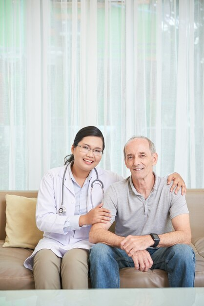Älterer mann und doktor, die auf sofa im wohnzimmer sitzt Kostenlose Fotos