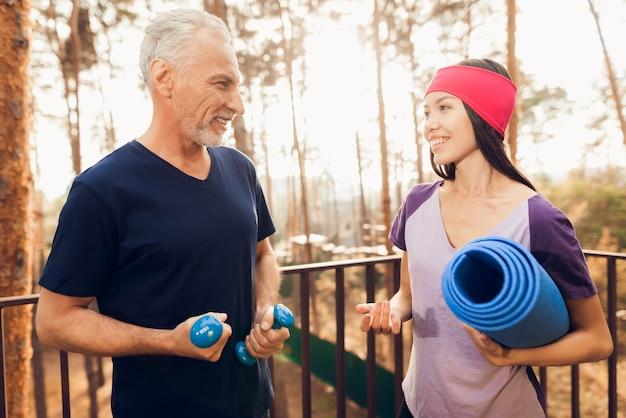 Älterer mann und fitnesstrainer sprechen Premium Fotos