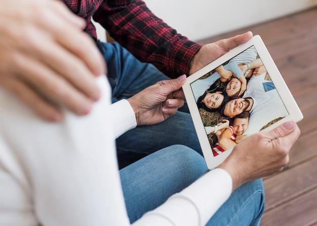 Älterer mann und frau, die durch bilder auf ihrer tablette schaut Kostenlose Fotos