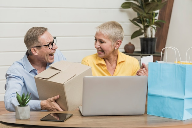 Älterer mann und frau, die ihre einkaufstaschen und kästen öffnet Kostenlose Fotos