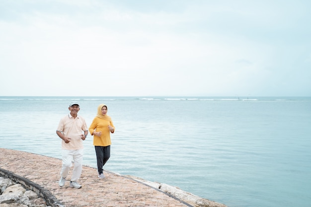 Älterer mann und frau, die zusammen am strand laufen Premium Fotos