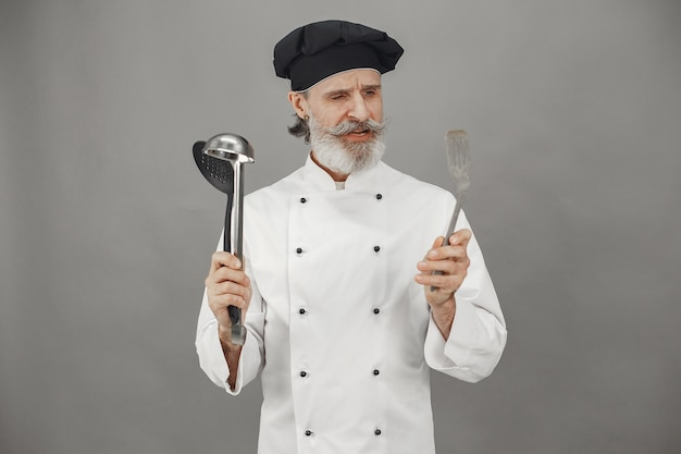 Älterer mann wählen schöpflöffel. chef in einer schwarzen mütze im kopf. professionelle herangehensweise an das geschäft. Kostenlose Fotos