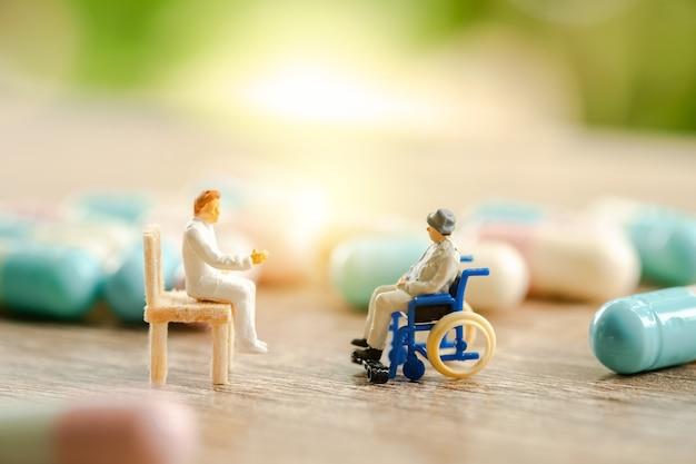 Älterer patient im rollstuhl, der mit doktor, medizinisches gesundheitswesenkonzept sich berät. Premium Fotos