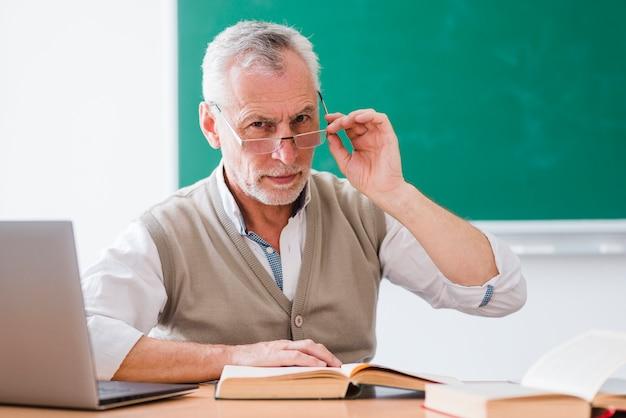 Älterer professor, der gläser korrigiert und kamera im klassenzimmer betrachtet Kostenlose Fotos