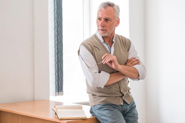 Älterer professor, der gläser nahe schreibtisch im klassenzimmer hält Kostenlose Fotos