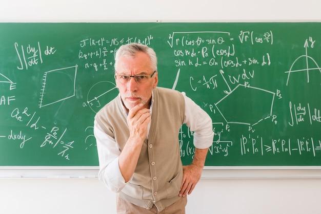 Älterer professor im klassenzimmer, das kamera mit frage betrachtet Kostenlose Fotos