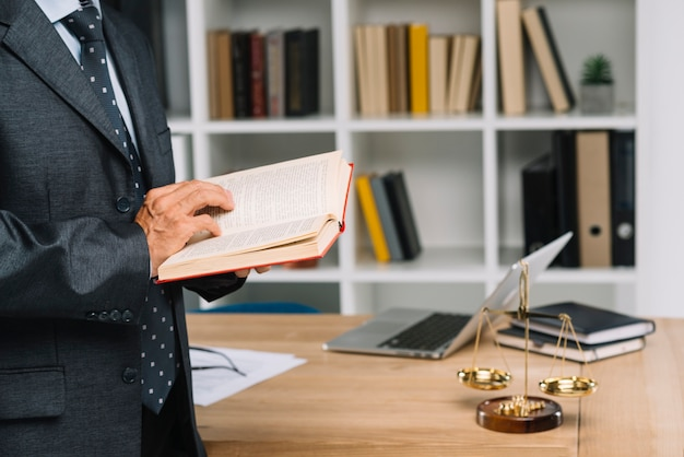 Älterer rechtsanwalt, der gesetzbuch im gerichtssaal liest Kostenlose Fotos