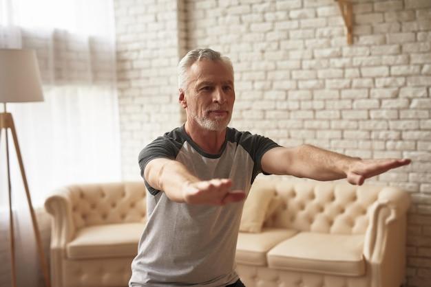 Älterer reifer sportler, der vorwärts hände ausdehnt. Premium Fotos