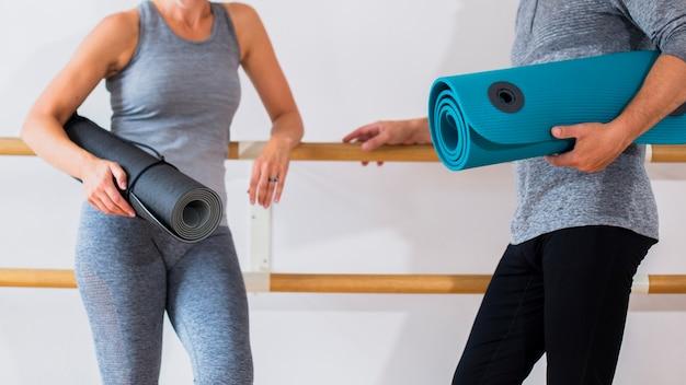 Älterer sitzmann und -frau, die yogamatten hält Kostenlose Fotos