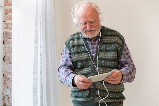 Älterer spielender musik des niedrigen winkels am telefon Kostenlose Fotos