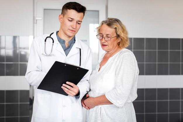 Älterer weiblicher patient, der doktorergebnisse betrachtet Kostenlose Fotos