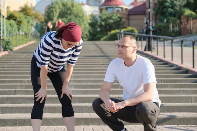 Älteres ehepaar in der stadt in der nähe der treppe, mann mittleren alters und frau in sportbekleidung Premium Fotos
