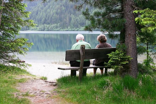 Älteres ehepaar sitzt auf einer bank am see Premium Fotos