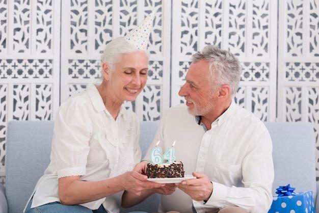 Älteres glückliches paar, das geburtstagskuchen mit kerze hält Kostenlose Fotos