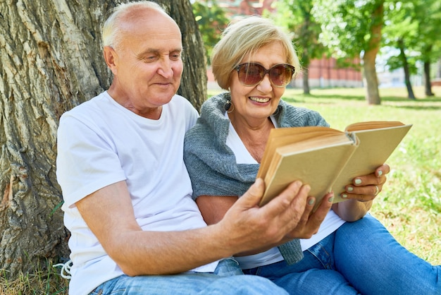 Älteres paar, das draußen ein buch liest Premium Fotos