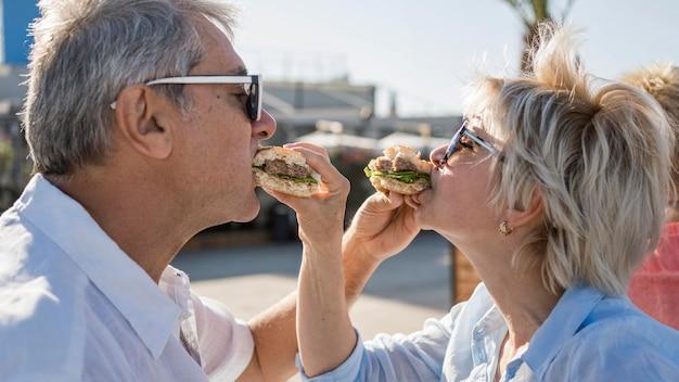 Älteres paar, das einen burger im freien genießt Kostenlose Fotos