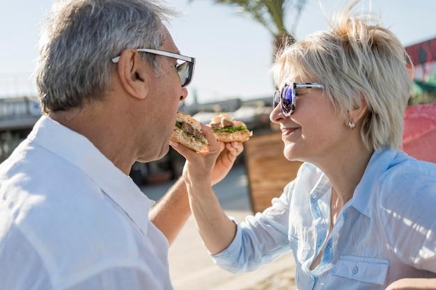 Älteres paar, das einen burger im freien isst Kostenlose Fotos