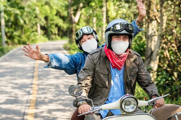 Älteres paar, das einen roller in der neuen normalen reise fährt Kostenlose Fotos