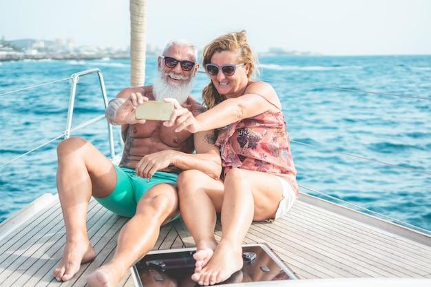 Älteres paar, das selfie auf segelboot während des luxus-ozeanreiseurlaubs tut Premium Fotos