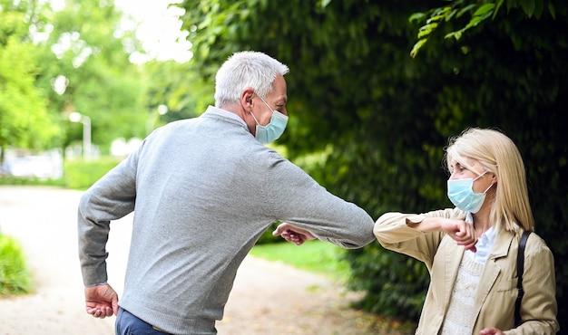 Älteres paar, das sich mit dem ellbogen trifft und begrüßt Premium Fotos