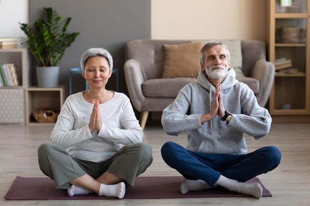 Älteres paar, das zu hause meditiert Premium Fotos