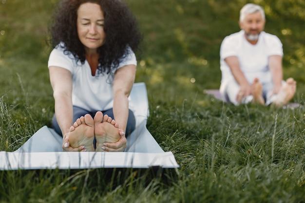 Älteres paar macht yoga im freien. dehnen im park während des sonnenaufgangs. brünette in einem weißen t-shirt. Kostenlose Fotos