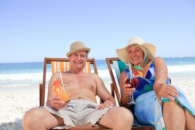 Älteres paar sitzt auf liegestühlen Premium Fotos