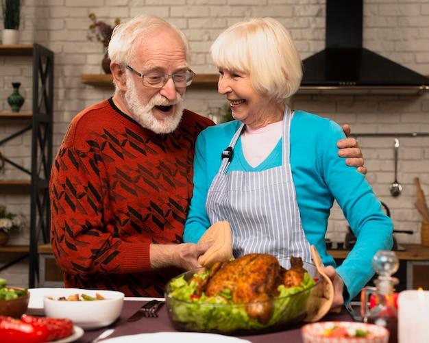 Älteres verheiratetes paar, das in der küche spielt und den truthahn hält Kostenlose Fotos