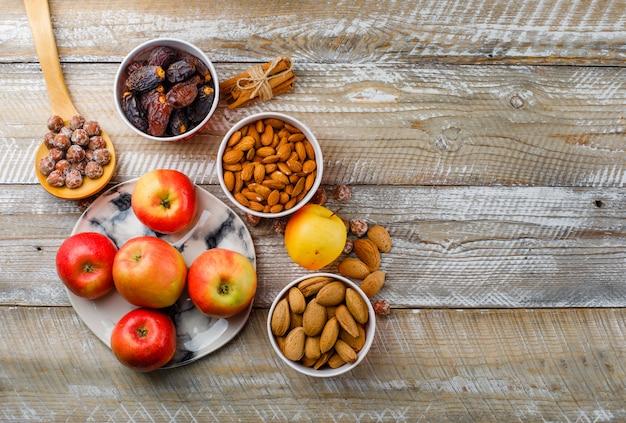 Äpfel in einem teller mit zimtstangen, datteln, geschälten und ungeschälten mandeln in schalen, nüssen in der holzlöffel-draufsicht auf einem hölzernen hintergrund Kostenlose Fotos