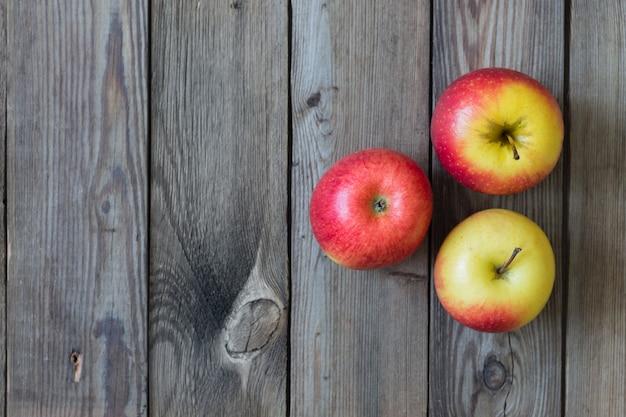 Äpfel und birnen liegen auf einem natürlichen holztisch. speicherplatz kopieren Premium Fotos