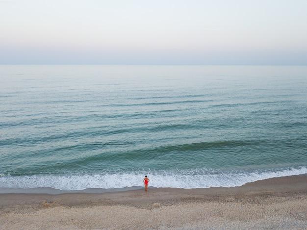 Aerial draufsicht auf frau im roten bikini in der nähe von meer am strand Premium Fotos