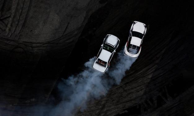 Aerial top view zwei autos treiben kampf auf asphalt-rennstrecke mit viel rauch. Premium Fotos