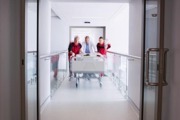 Ärzte schieben notbahre bett im korridor Kostenlose Fotos