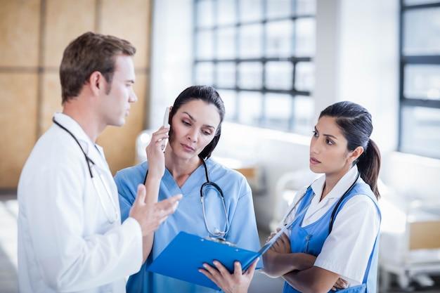 Ärzteteam, das zusammen den bericht am krankenhaus bespricht Premium Fotos