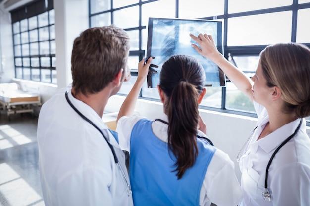 Ärzteteam, das zusammen röntgenstrahl krankenhaus betrachtet Premium Fotos