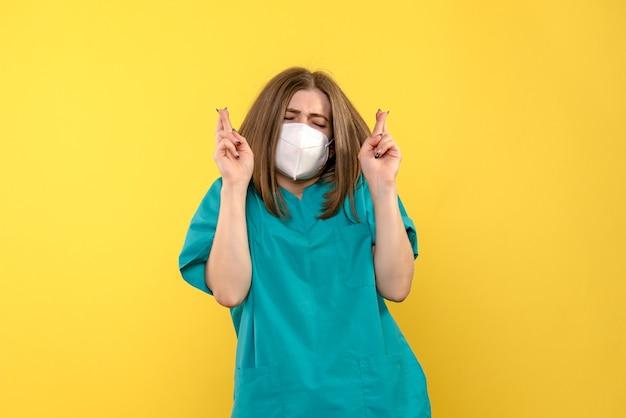 Ärztin der vorderansicht, die auf gelben raum hofft Kostenlose Fotos