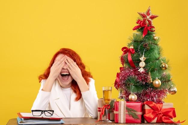 Ärztin der vorderansicht, die hinter tisch mit weihnachtsgeschenken auf gelbem schreibtisch sitzt Kostenlose Fotos