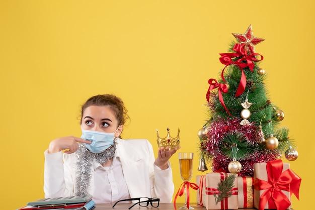 Ärztin der vorderansicht, die in der sterilen maske hält krone im gelben hintergrund mit weihnachtsbaum und geschenkboxen hält Kostenlose Fotos