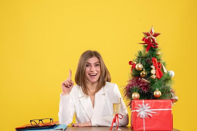 Ärztin der vorderansicht, die vor ihrem tisch auf gelbem hintergrund mit weihnachtsbaum und geschenkboxen sitzt Kostenlose Fotos
