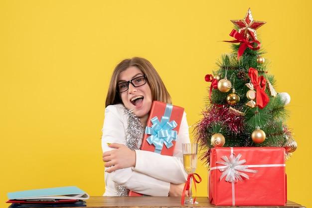 Ärztin der vorderansicht, die vor tisch mit geschenken und baum auf gelbem hintergrund mit weihnachtsbaum und geschenkboxen sitzt Kostenlose Fotos