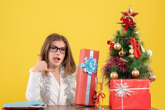 Ärztin der vorderansicht, die vor tisch mit geschenken und baum auf gelbem schreibtisch mit weihnachtsbaum und geschenkboxen sitzt Kostenlose Fotos