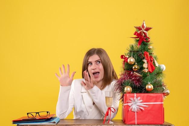 Ärztin der vorderansicht, die vor tisch mit weihnachtsgeschenken und baum auf gelbem hintergrund sitzt Kostenlose Fotos